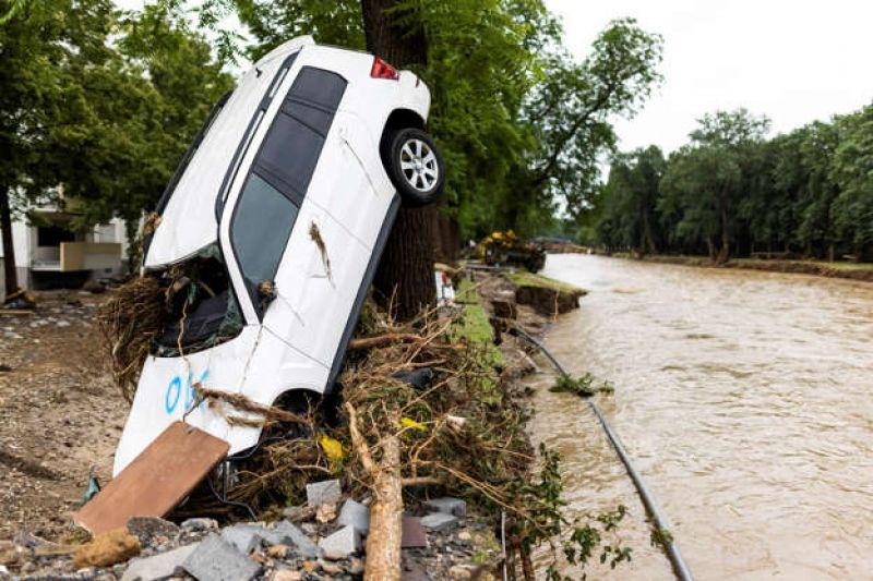 a-car-washed-up-by-the-flood-leans-against-a-tree-while-the-river-ahr-can-be-seen-in-the-background-in-bad-neuenahr-germany-friday-july-16-2021-ccfd18055be6438c9f317fa5883214c31626512922.jpg